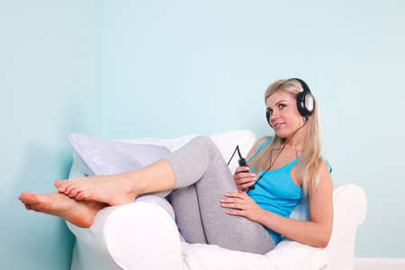 Blond woman sat in an armchair with headphones on listening to music. Stock Photo - 7057008