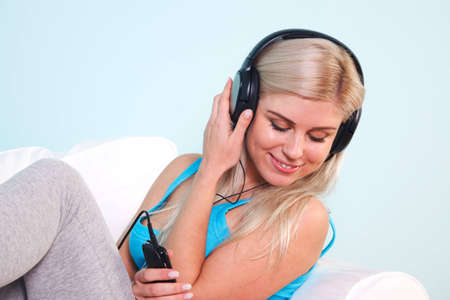 Young blond woman sat in an armchair listening to music on her mp3 player through headphones Stock Photo - 7057024