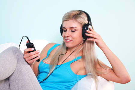 Young blond woman sat in an armchair listening to music on her mp3 player through headphones Stock Photo - 7057087