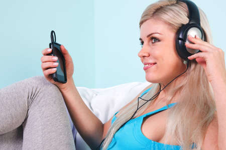 Young blond woman sat in an armchair listening to music on her mp3 player through headphones Stock Photo - 7057093