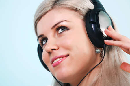 Headshot of a young pretty blond woman wearing headphones listening to music  Stock Photo - 7057025