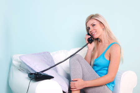 Young blond woman sat in an armchair talking on the telephone Stock Photo - 7057018