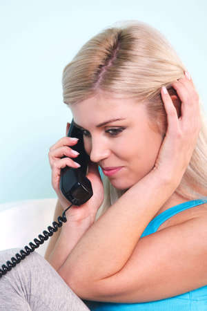 Young blond woman sat in an armchair talking on the telephone Stock Photo - 7057092