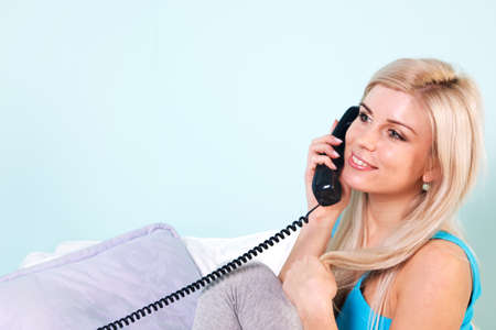 Young blond woman sat in an armchair talking on the telephone photo