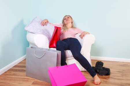 slumped: A blond woman slumped in an armchair exhausted after a shopping trip.