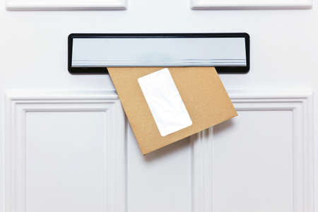 Brown envelope in a front door letterbox blank window for you to add your own name and address details. photo