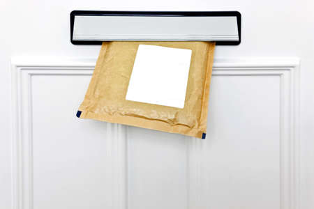 A padded envelope in the letterbox of a white front door, blank label for you to add your own name and address. photo