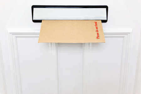 Please do not bend envelope in a letterbox of a white front door, space to add your own text. photo