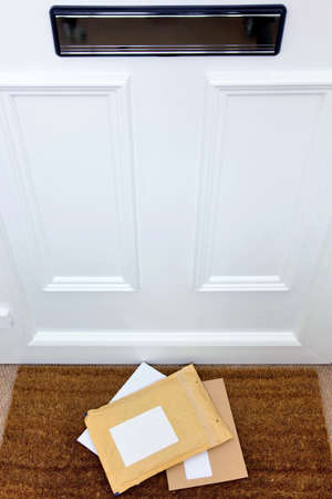 letterbox: Letters and a package lying on a doormat, blank labels to add your own name and address, focus on the letters. Stock Photo