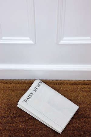 broadsheet: Newspaper lying on a doormat, blank to add your own text. Generic titles added by me. Stock Photo