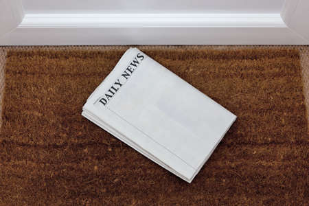 broadsheet newspaper: Newspaper lying on a doormat, blank to add your own text. Generic titles added by me. Stock Photo