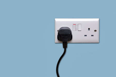 Double electrical power socket and single plug switched on, blue background. photo