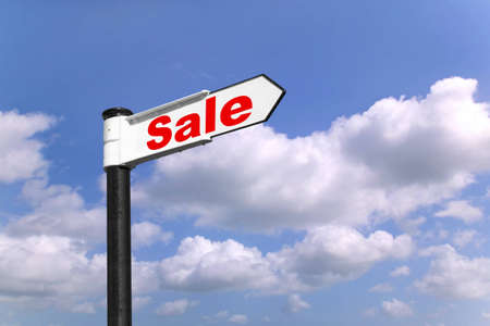 Black and white signpost with the word Sale against a blue cloudy sky photo