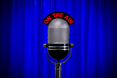 Retro microphone on stage against a blue curtain with spotlight effect photo