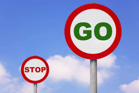 Round roadsigns with GO and STOP on them against a blue cloudy sky. photo