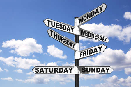day time: A signpost with the seven days of the week on the directional arrows, against a bright blue cloudy sky. Good image for a 247 related theme.
