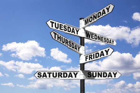 Ein Schild mit den sieben Tagen der Woche auf die Richtungspfeile, against a bright blue cloudy Sky. Gutes Image für ein 24/7 Beiträge zu diesem Thema.