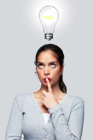 eyes looking up: Concept image of a woman with a bright idea, illustration of a lightbulb above her head.