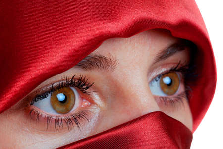 Woman with brown eyes wearing a red veil looking away from camera. photo