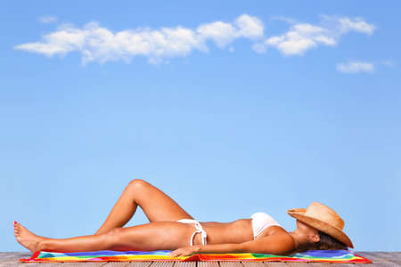 sun tan: Woman in a white bikini lying on a wooden deck sunbathing with a straw hat over her head.