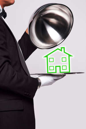 Butler lifting the cloche from a silver serving tray to reveal a house illustration, good image for housing themes. Stock Illustration - 7971158