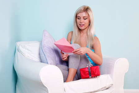 post cards: Blond woman sat in an armchair opening her birthday card