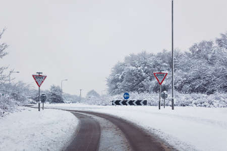hants: Shot of a road on the approach to a roundabout after a heavy snow fall, Give Way signs