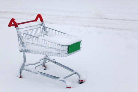 An abandoned shopping trolley in the snow photo
