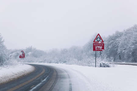 Road with Reduce speed now sign during snow fall of winter 2010 photo