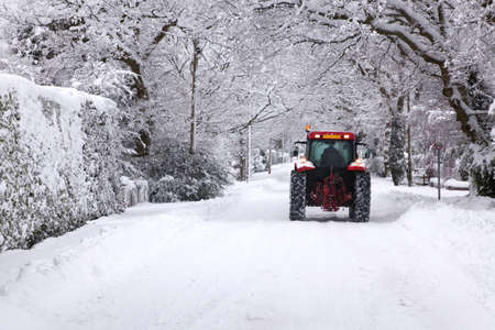 A red tractor driving down a snow covered UK road during the winter snowfall winter in January 2010 Stock Photo