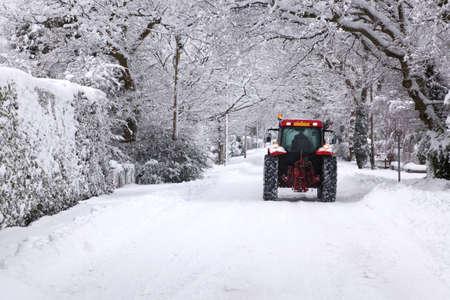 blizzard: Ein roter Traktor fahren hinunter eine Schnee bedeckt UK Stra�e im Winter Schneefall Winter im Januar 2010 Lizenzfreie Bilder
