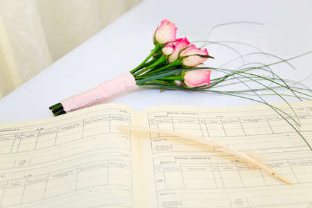 registry: A wedding register and quill with a bouquet of pink roses on a white table. Stock Photo