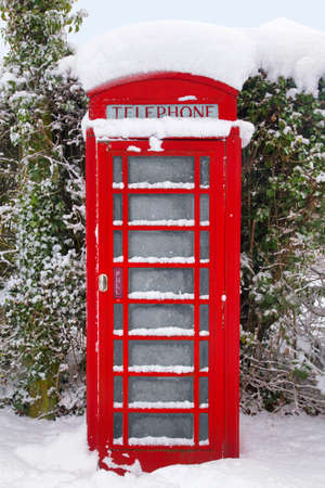 phonebooth: A traditional red British telephone kiosk in the snow at winter time.