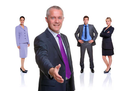 A manager offering to shake your hand with a business team behind, isolated on a white background. photo