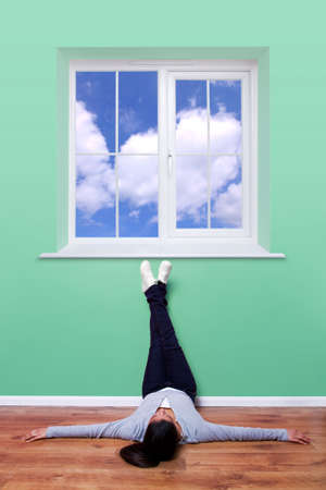 woman window: Young woman lying on the floor with her feet up the wall thinking as she looks out of the window to a clear blue sky.