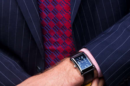 close up image: Close up image of a businessman checking the time on his wrist watch. Stock Photo