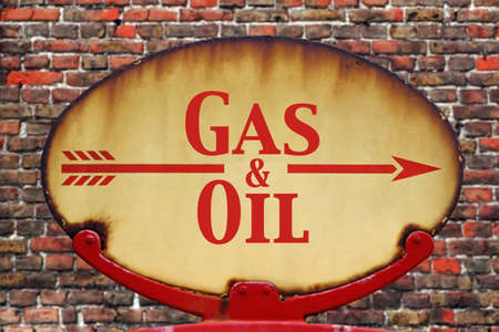 of yesteryear: A rusty old retro arrow sign with the text Gas and Oil Stock Photo