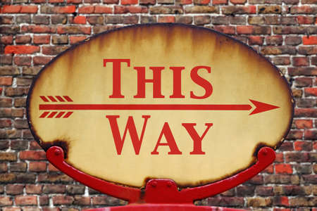 A rusty old retro arrow sign with the text This Way