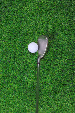 Photo of a Golf ball and iron club on grass photo