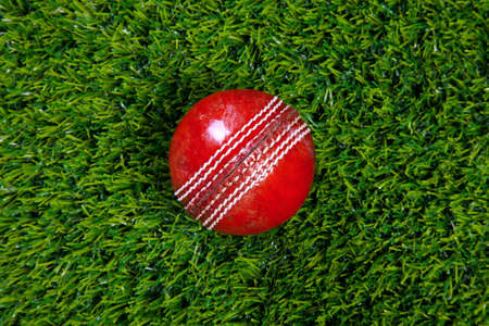 cricket sport: Photo of a red leather cricket ball with stitched seams on grass