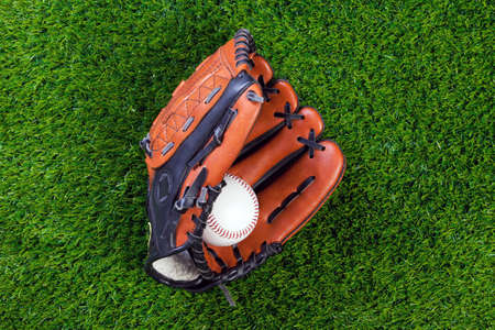 gant de baseball: Photo of a baseball glove and ball on grass.