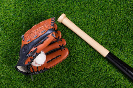 catcher's mitt: Photo of a Baseball glove bat and ball on grass