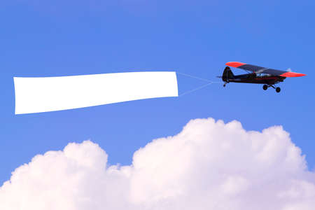 An airplane flying through the sky pulling a blank white banner to add your own message. Stock Photo - 8394359