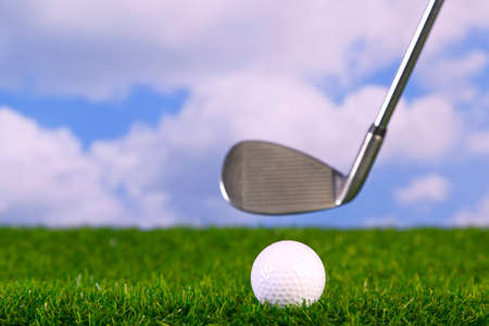 Surface level photo of an iron golf club in mid swing about to hit a ball on the fairway. photo