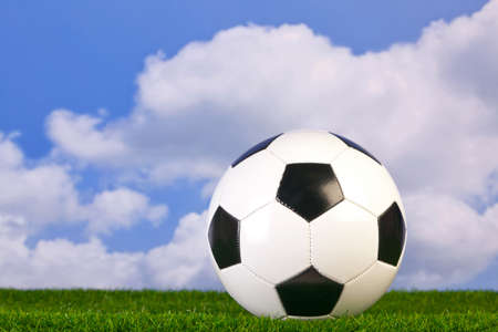 Photo of a football on grass with sky background. photo