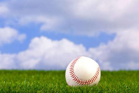campo de beisbol: Foto de una pelota de béisbol sobre césped con fondo de cielo. Foto de archivo