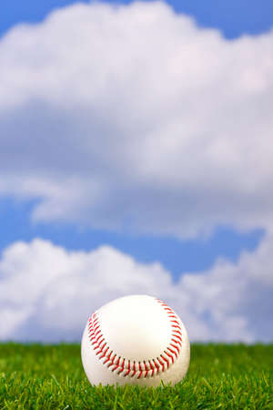 baseball ball: Photo of a baseball on grass with sky background.