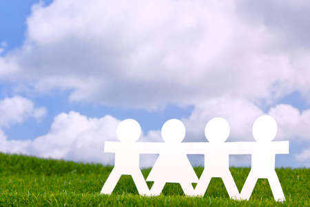 Concept image of paper people holding hands in a field with a blue sky background. Stock Photo