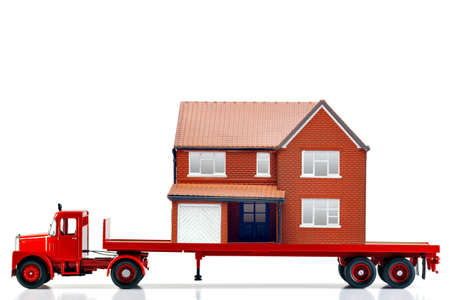 relocate: A flatbed articulated lorry loaded with a house isolated on a white background. Both are models. Good image for moving home themes. Stock Photo