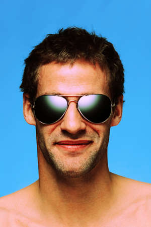 procesed: Headshot of a caucasian man in his late twenties with designer stubble wearing aviator sunglasses taken against a plain blue background, cross processed colour effect. Stock Photo